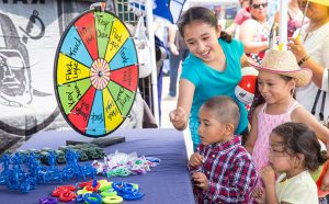 Kids at vendor booth spinning wheel